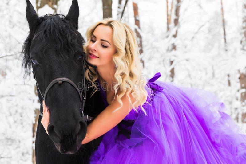 Jonge vrouw in lange kleding die een paard in de winter berijden stock foto