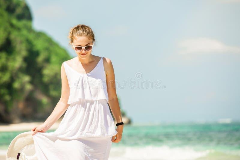 Jonge vrouw in lange witte de hoedengangen van de kledingsholding royalty-vrije stock fotografie