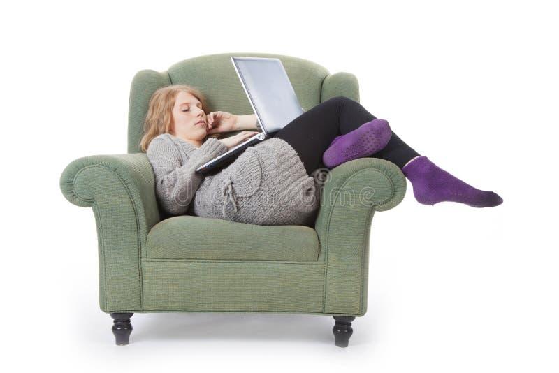 Jonge vrouw in leunstoel met laptop stock afbeelding