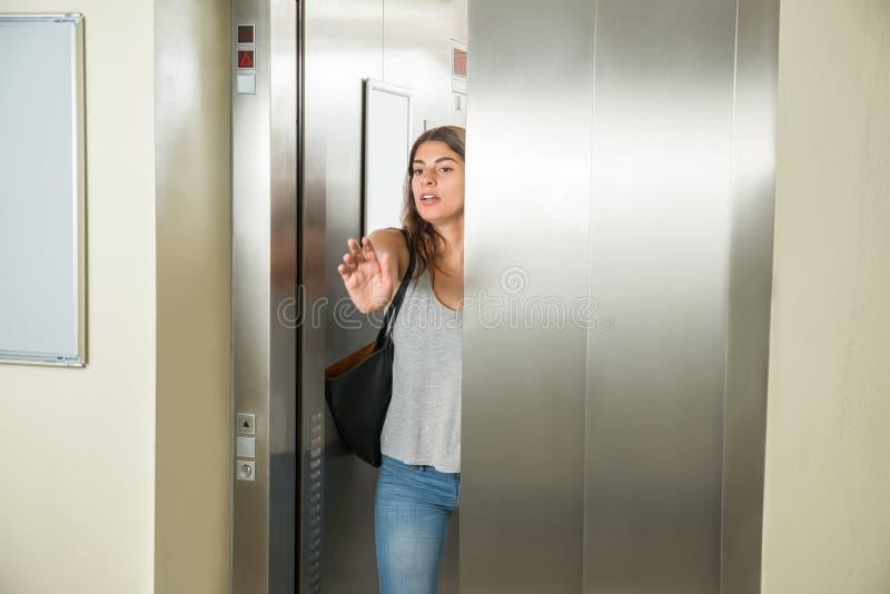 Jonge vrouw in lift stock afbeelding