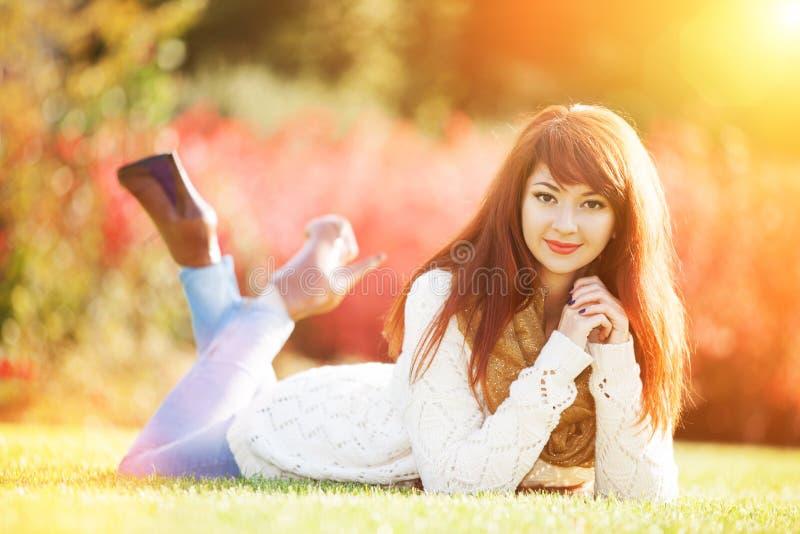Jonge vrouw loopt in het park Schoonheid in de natuur met een kleurrijke achtergrond, bomen en bladeren tijdens het herfstseizoen stock afbeeldingen