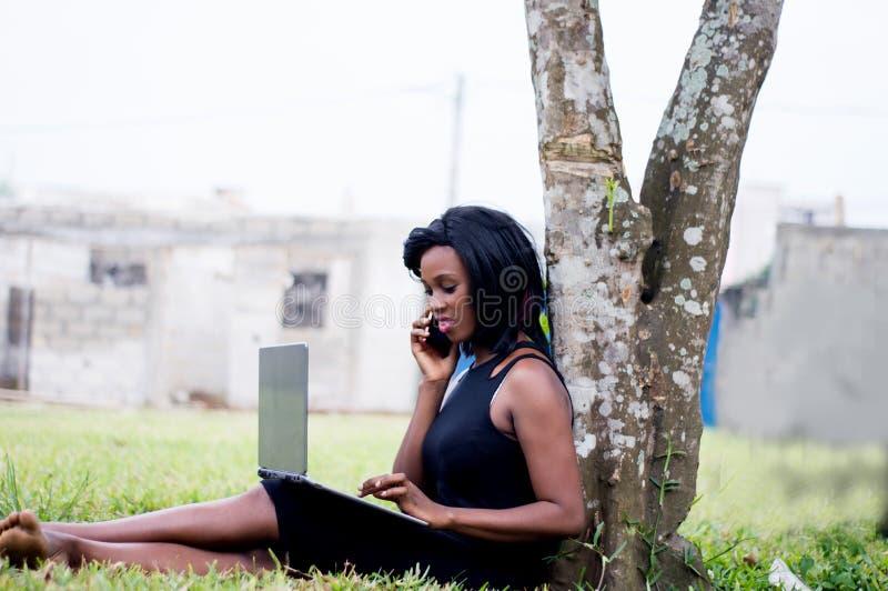 Jonge vrouw in mededeling en het gebruiken van een computer stock foto