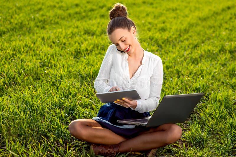 Jonge vrouw, meisje met laptop werken, tablet en telefoon die in groen stock afbeelding