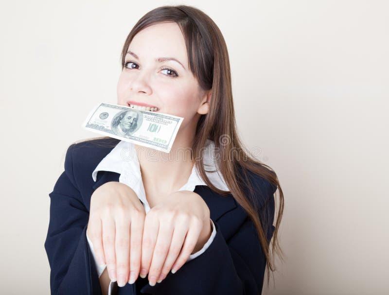 Jonge vrouw met 100 dollars in haar mond