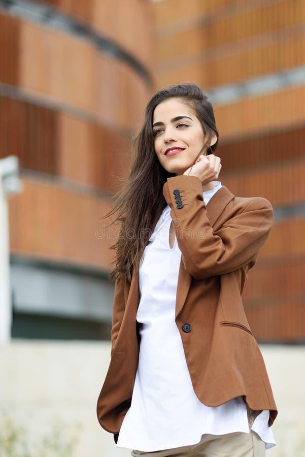 Jonge vrouw met aardig haar die zich buiten de bureaubouw bevinden royalty-vrije stock fotografie
