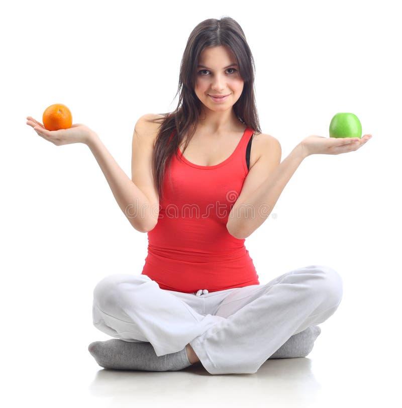 Jonge vrouw met appel en sinaasappel. Geïsoleerd royalty-vrije stock afbeelding