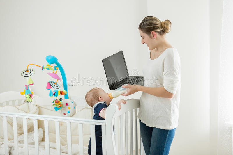 Jonge vrouw met baby het werken thuis aan laptop royalty-vrije stock foto