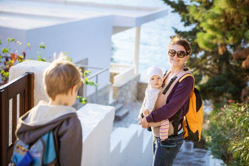 Jonge vrouw met babydochter en peuterzoon die onderaan treden in kuststad lopen royalty-vrije stock afbeelding