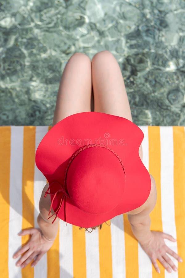 Jonge vrouw met blauwe bikini en rode hoed op een handdoek over glashelder blauw water royalty-vrije stock foto
