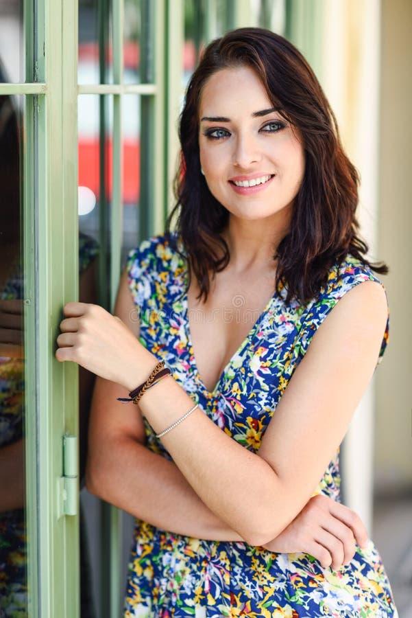 Jonge vrouw met blauwe ogen die zich naast mooie deur bevinden Meisje die bloemkleding op stedelijke achtergrond dragen Schoonhei royalty-vrije stock afbeeldingen
