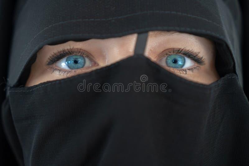 Jonge vrouw met blauwe ogen in zwarte nibe dichte omhooggaand Het meisje in burqa Concept van de mensen het godsdienstige levenss royalty-vrije stock foto