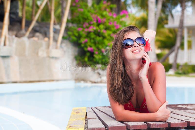 Jonge vrouw met bloem in haar enjoyng zonnige dag in luxepool stock foto's