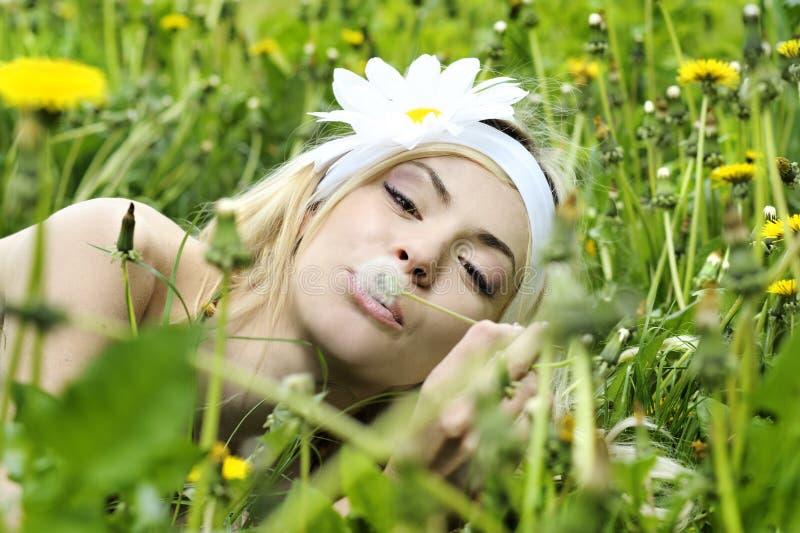 Jonge vrouw met bloem in haar haar die op een paardebloem blazen. royalty-vrije stock afbeeldingen