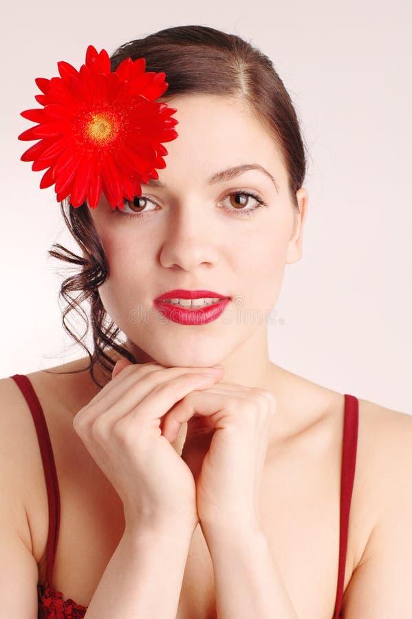 Jonge vrouw met bloemen in haar haar royalty-vrije stock afbeeldingen