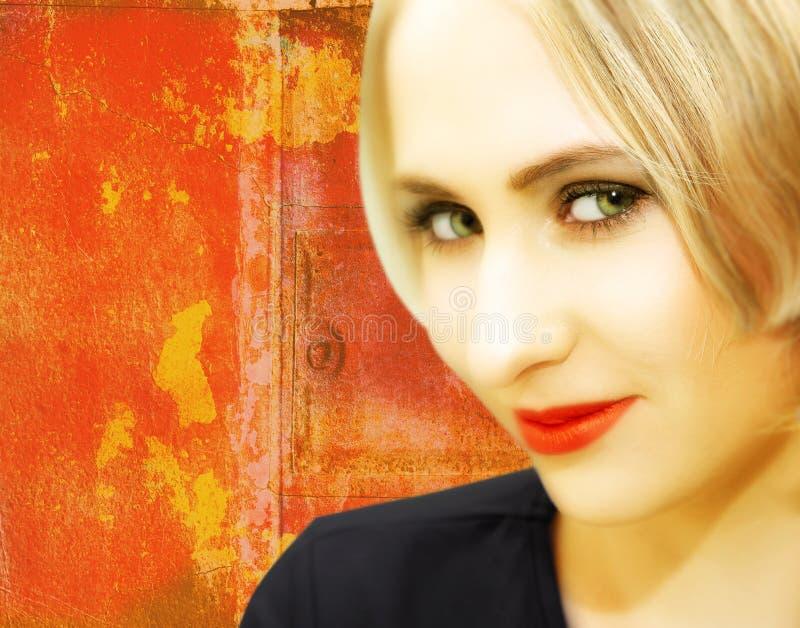 Jonge vrouw met blond haar op grungy rode achtergrond stock foto's