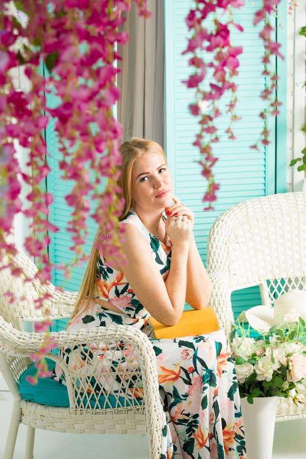 Jonge vrouw met boek in de zomerterras stock afbeelding