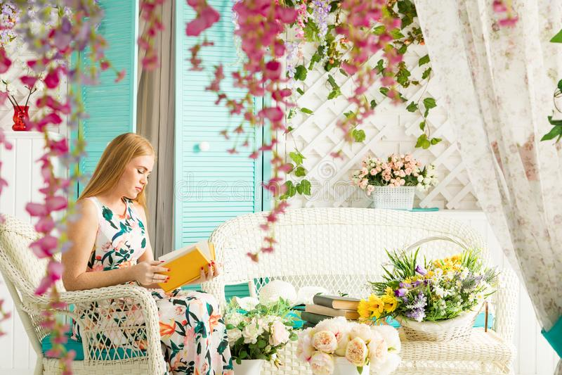 Jonge vrouw met boek in de zomerterras stock foto's