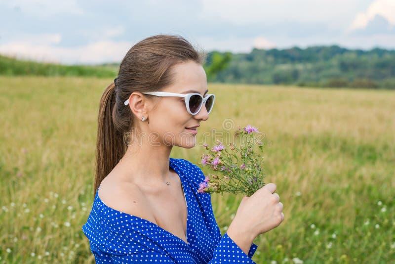 Jonge vrouw met boeket van bloemen in zonnebril in een weide royalty-vrije stock afbeeldingen
