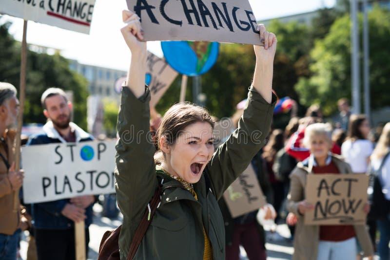 Jonge vrouw met bordje en poster over wereldwijde staking van klimaatverandering royalty-vrije stock fotografie