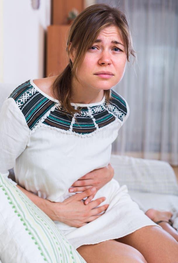 Jonge vrouw met buikpijn stock foto