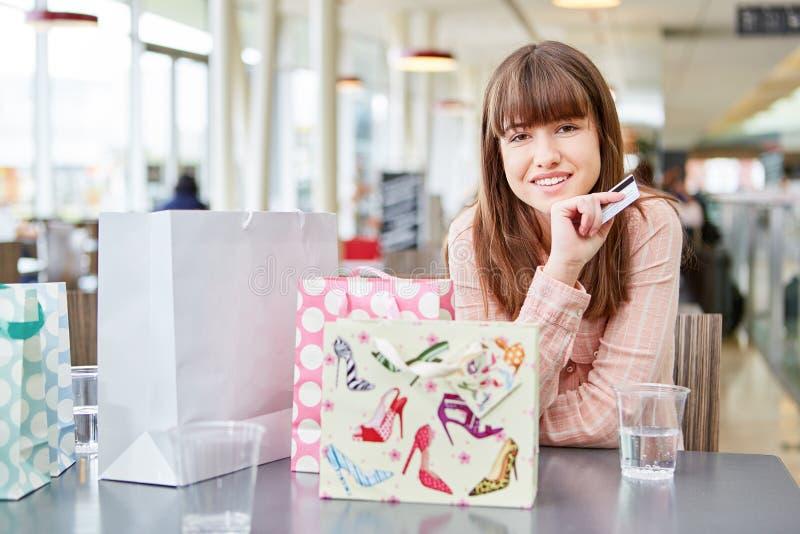 Jonge vrouw met creditcard en vele zakken stock fotografie