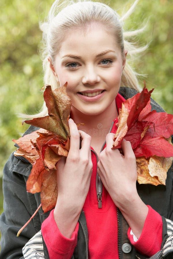 Jonge vrouw met de herfstbladeren stock foto's