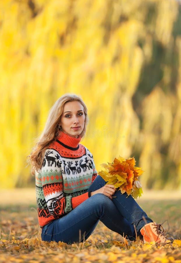 Jonge vrouw met de herfstbladeren royalty-vrije stock afbeelding