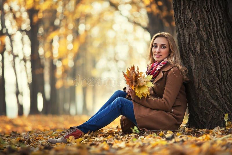 Jonge vrouw met de herfstbladeren royalty-vrije stock foto