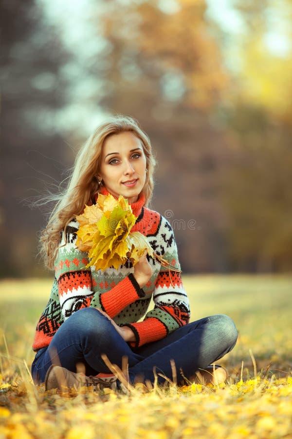 Jonge vrouw met de herfstbladeren stock afbeeldingen