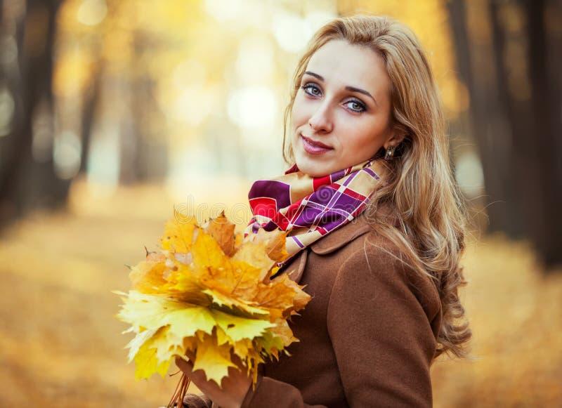 Jonge vrouw met de herfstbladeren royalty-vrije stock afbeeldingen