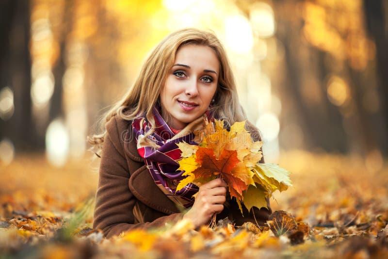 Jonge vrouw met de herfstbladeren stock foto