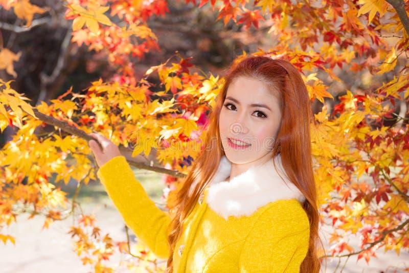 Jonge vrouw met de herfstbladeren in esdoorntuin stock fotografie