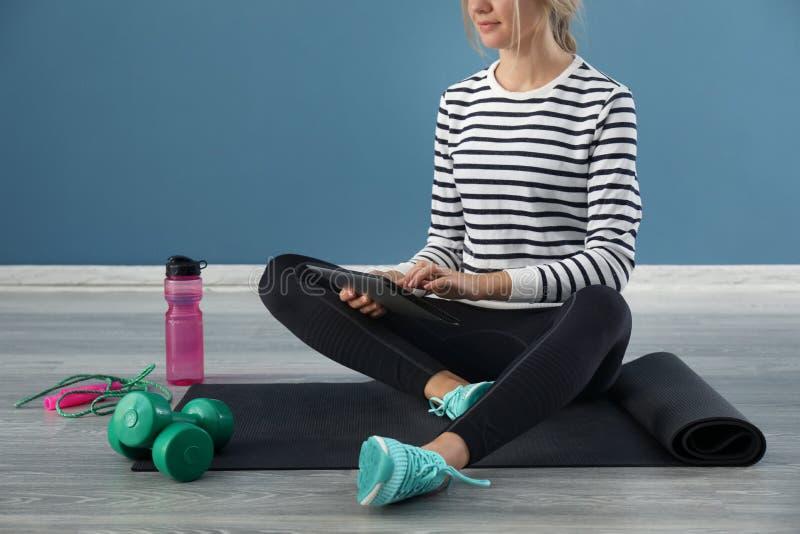 Jonge vrouw met de zitting van tabletpc op yogamat binnen Concept evenwicht tussen rust en het werk stock afbeeldingen