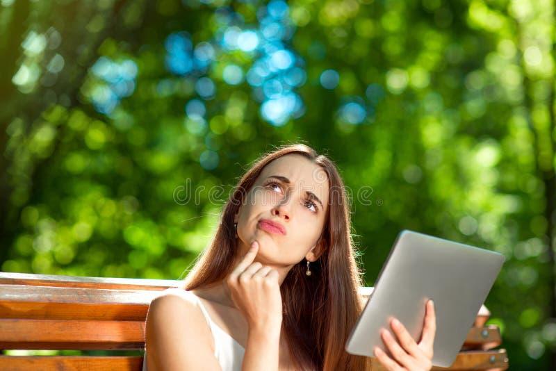 Jonge vrouw met digitale tablet in het park royalty-vrije stock afbeeldingen