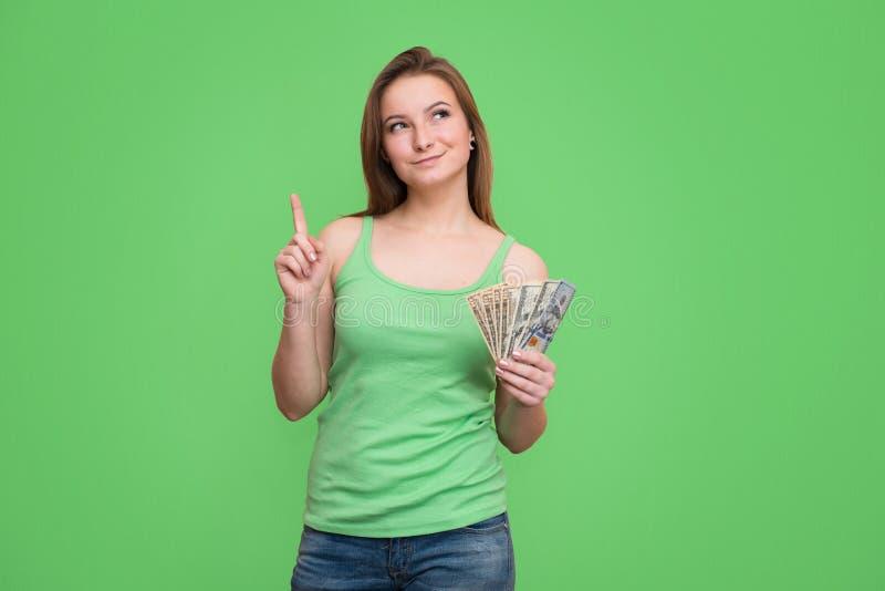 Jonge vrouw met dollars in haar handen denken, geïsoleerd op gree stock afbeelding