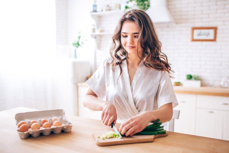 Jonge vrouw met donker haar die zich in keuken en knipsel groene ui bevinden Eieren bovendien Ochtenddaglicht Alleen in keuken royalty-vrije stock fotografie