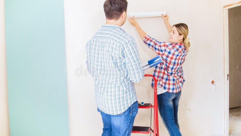 Jonge vrouw met echtgenoot die kleur van behang in nieuw huis bekijken stock fotografie