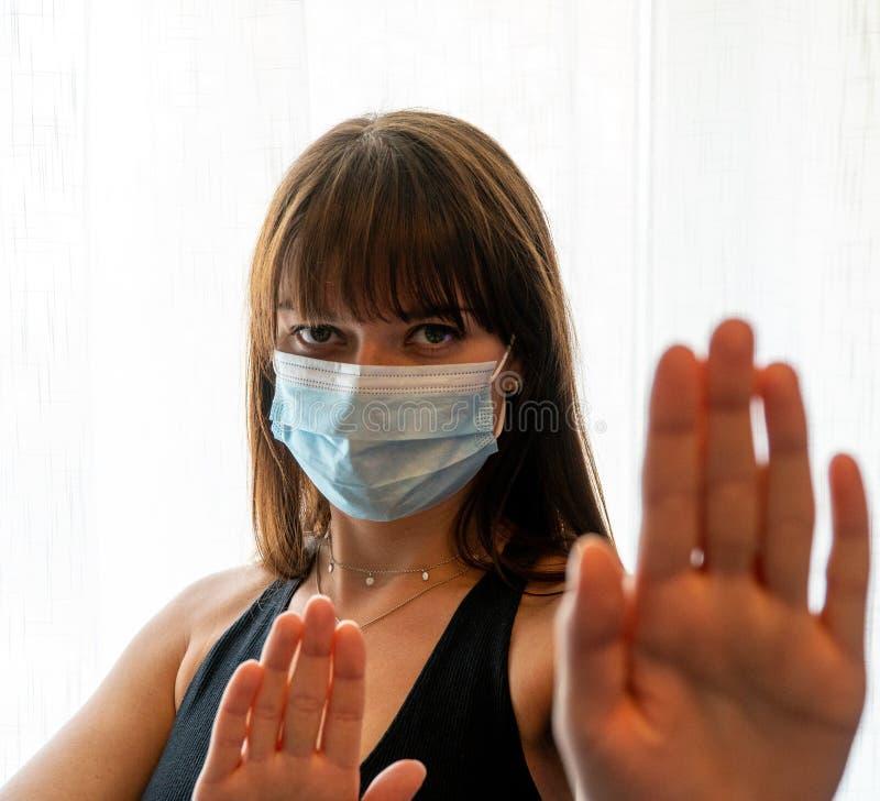 Jonge vrouw met een facemask die de handen omhoog houdt om de kijker te laten stoppen royalty-vrije stock foto