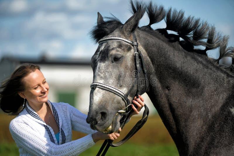 Jonge vrouw met een grijs paard stock afbeeldingen
