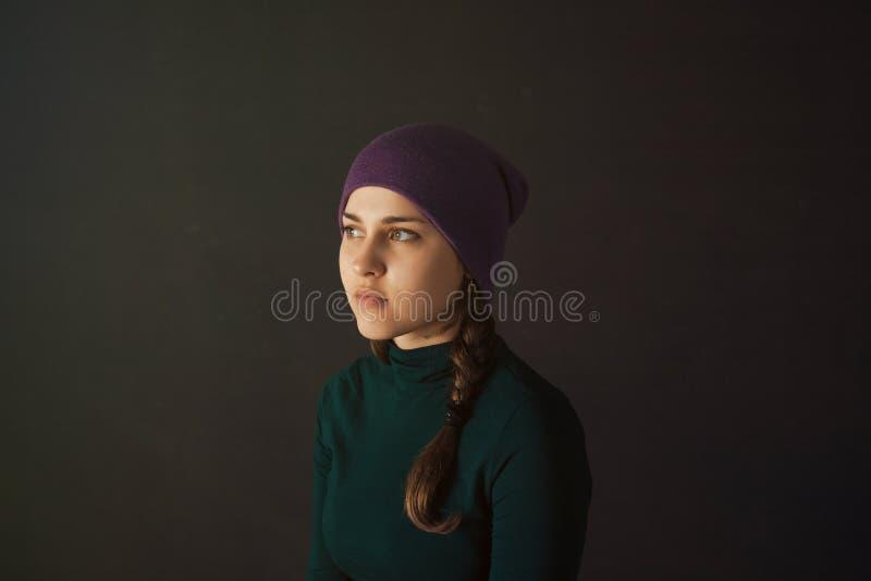 Jonge vrouw met een hoed op een donkere achtergrond stock afbeeldingen