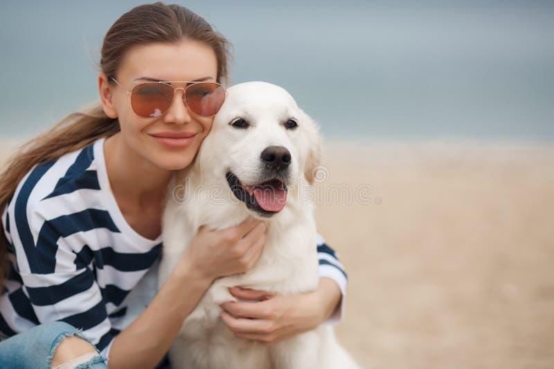 Jonge vrouw met een hond op een verlaten strand stock afbeelding