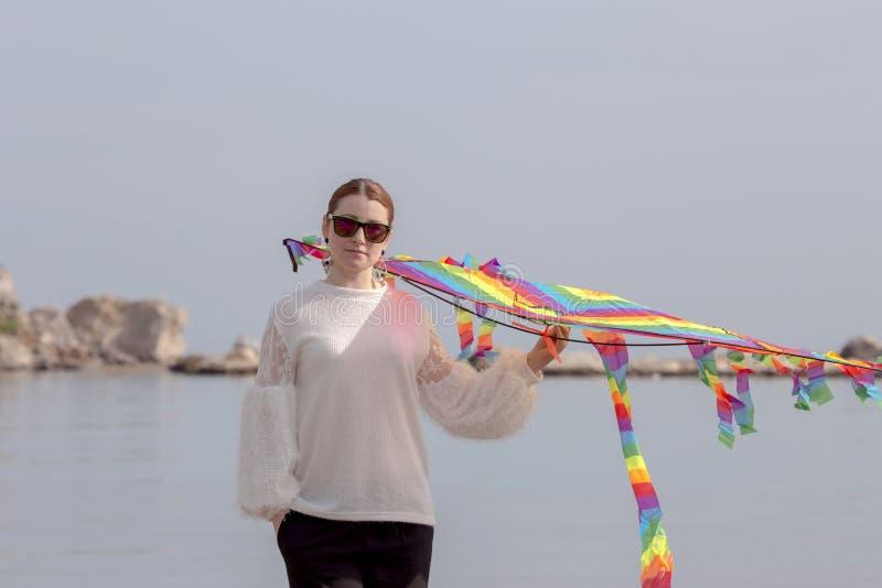 Jonge vrouw met een luchtige vlieger royalty-vrije stock afbeelding