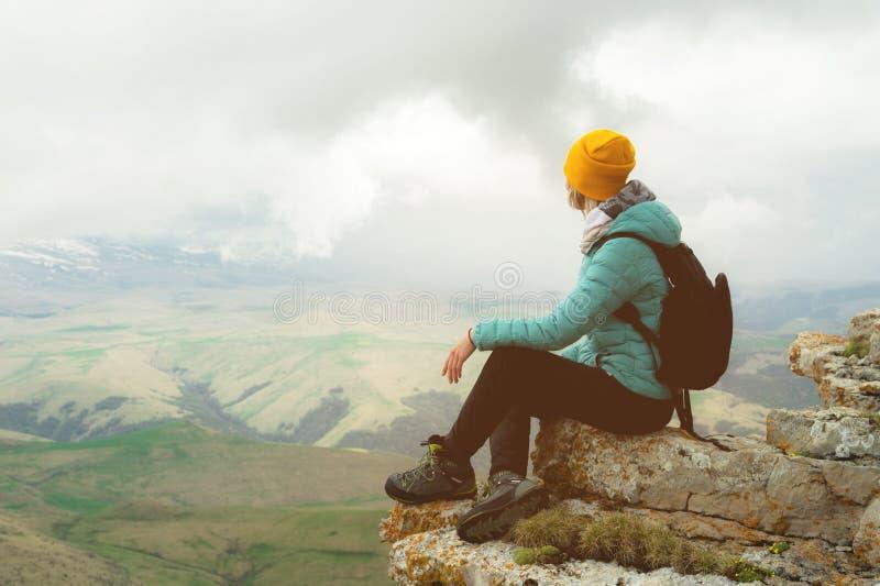 Jonge vrouw met een rugzak die pensively op de rand van een rots zitten en de hemel met wolken bekijken stock afbeelding