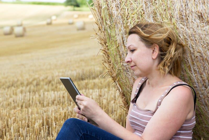 Jonge vrouw met een tablet op een gebied stock fotografie