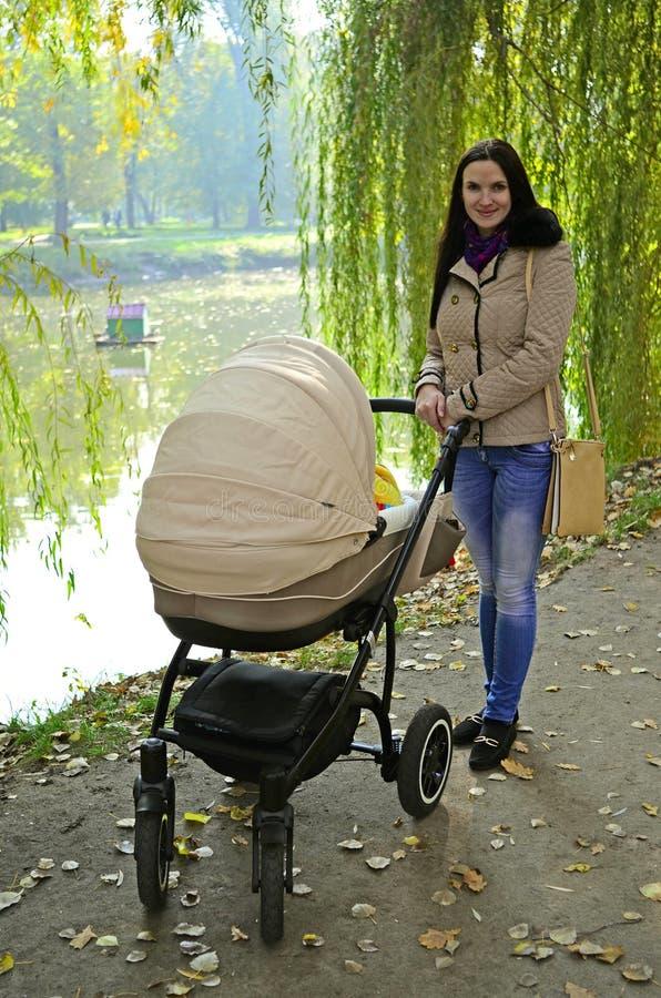 Jonge vrouw met een wandelwagen in een stadspark Gelukkige moeder met een babywandelwagen royalty-vrije stock fotografie