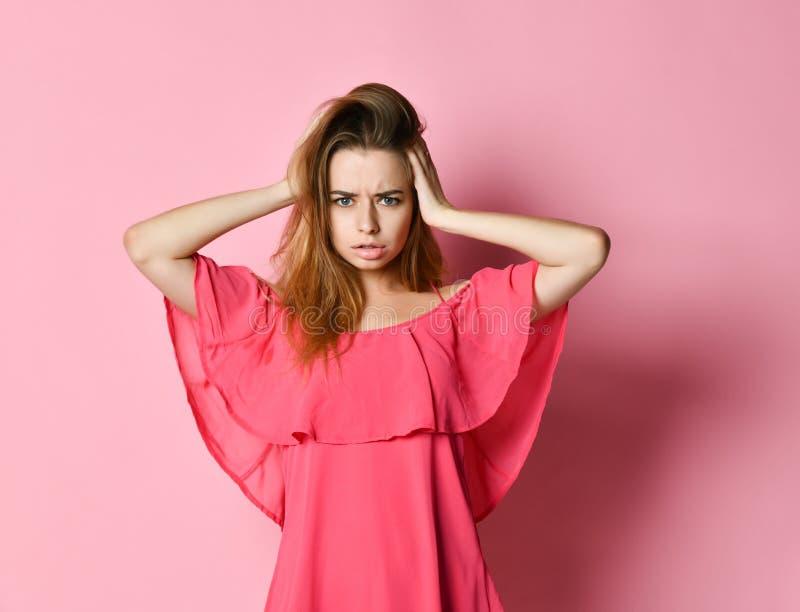 Jonge vrouw met eerlijk haar in roze kleding het fronsen het grijpen hoofd stock fotografie