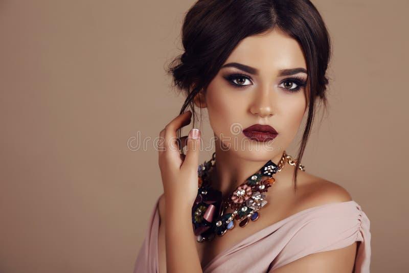 Jonge vrouw met elegant kapsel en luxueuze halsband stock foto's