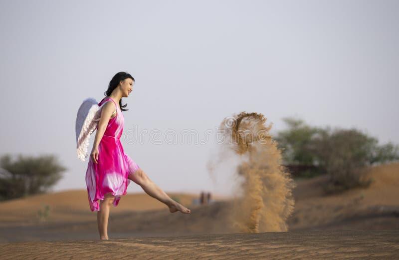 Jonge vrouw met engelenvleugels in een woestijn stock afbeelding