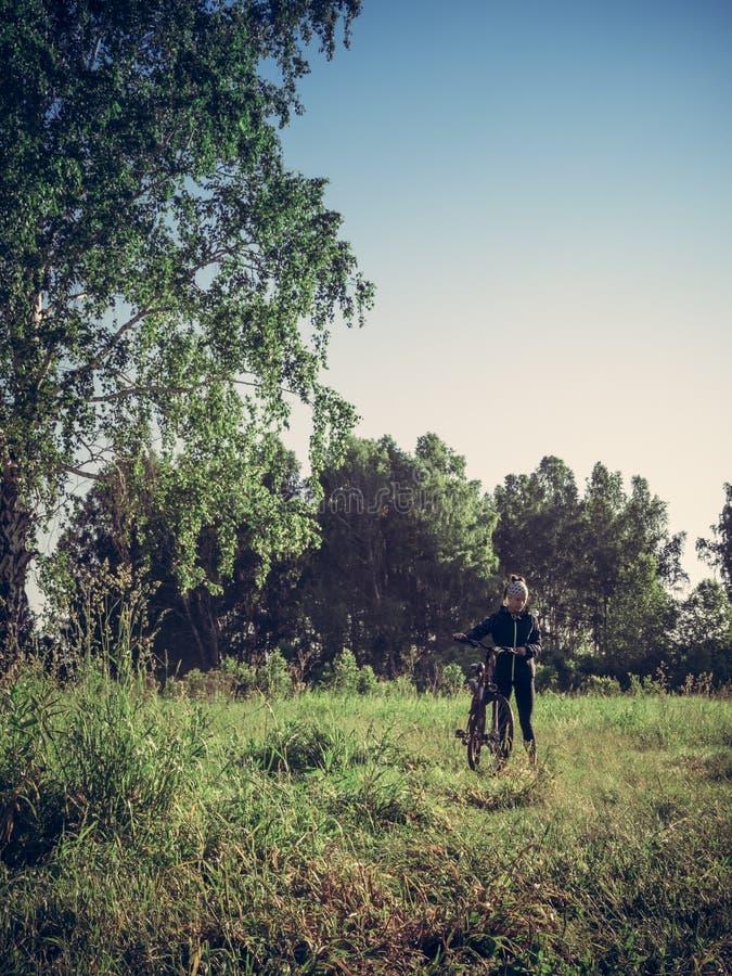 Jonge vrouw met fiets in het bos stock fotografie