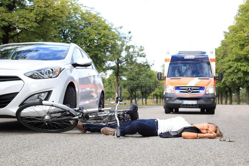 Jonge Vrouw met fietsongeval en komende ziekenwagenauto stock afbeeldingen